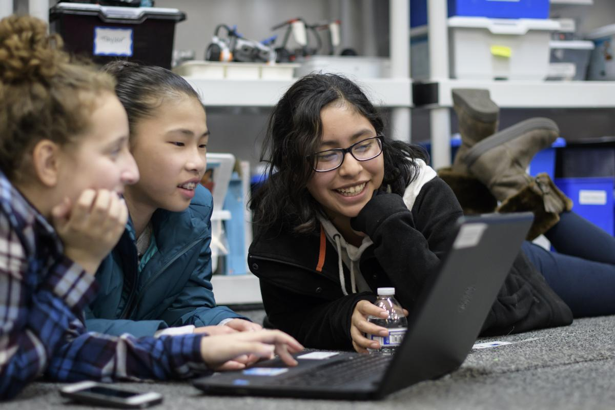 Girls use a laptop at a Girls Who Code club.
