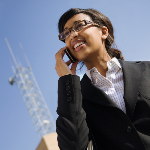 A woman talks on a cell phone with an antenna in the background.