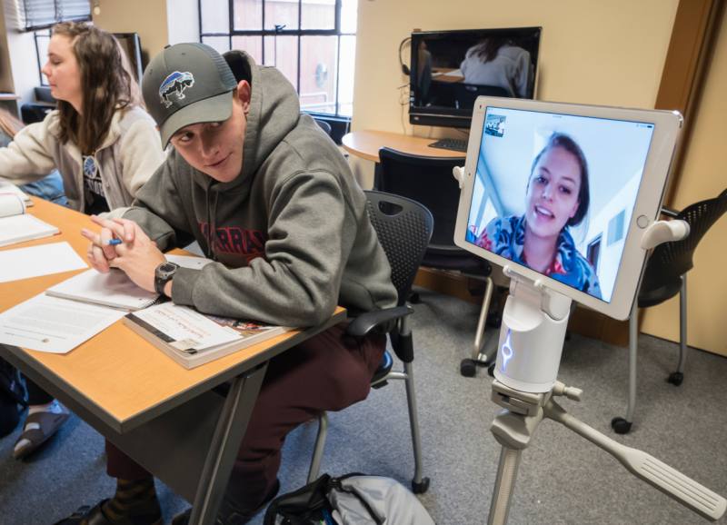 A remote student attends class on Kubi and iPad setup, interacts with face-to-face student.