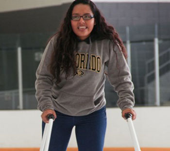 A student skates on an ice rink with the help of a skating walker.